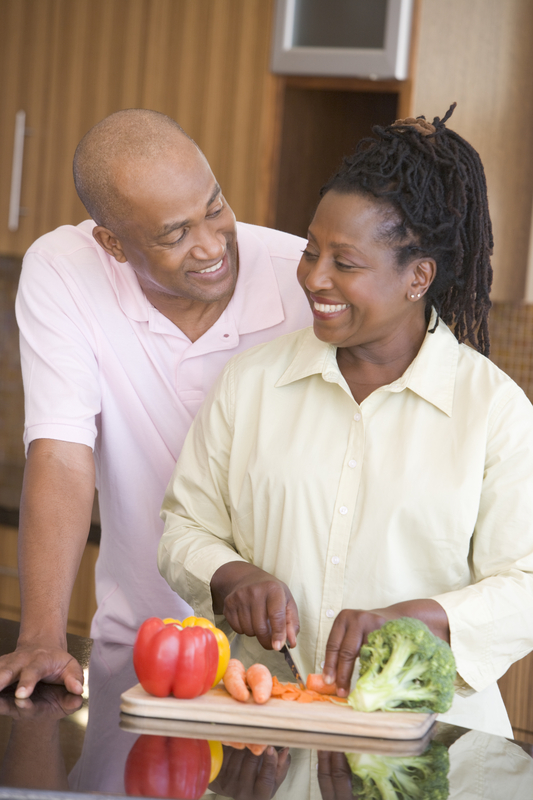 Older couple smiling and standing together in their kitchen. Women is cutting vegetables.