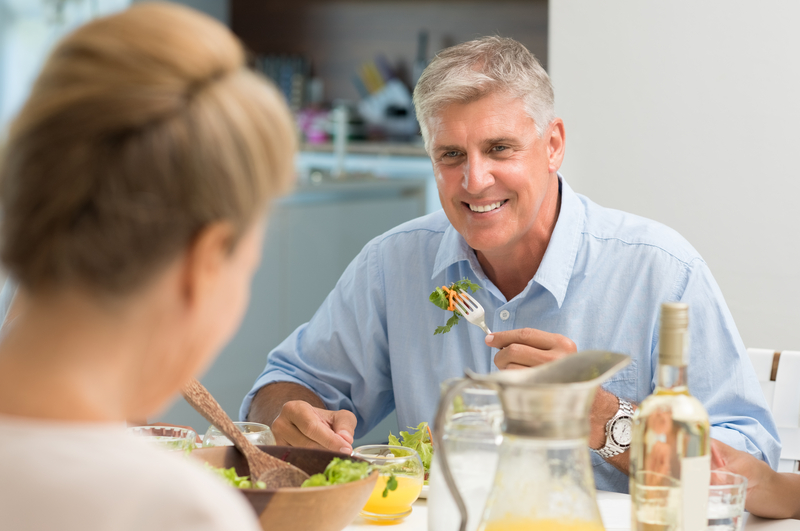 Older man sitting across the table from a women. They are eating salad.