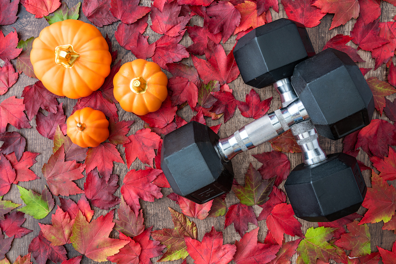 Three small pumpkins and two overlapping dumbbells in a pile of red leaves.
