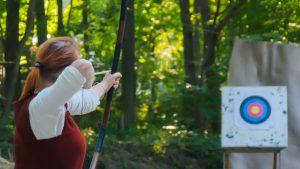 Women shooting arrow at a target.