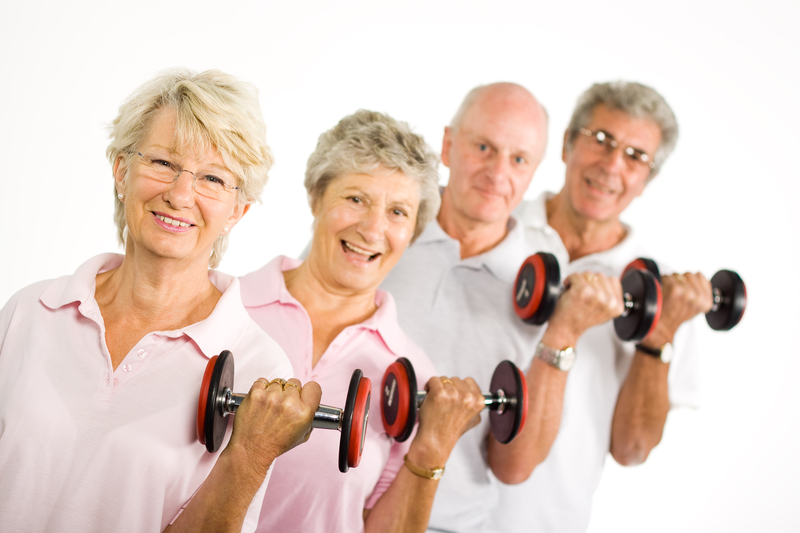 Image of four elder people lifting weights in a row.