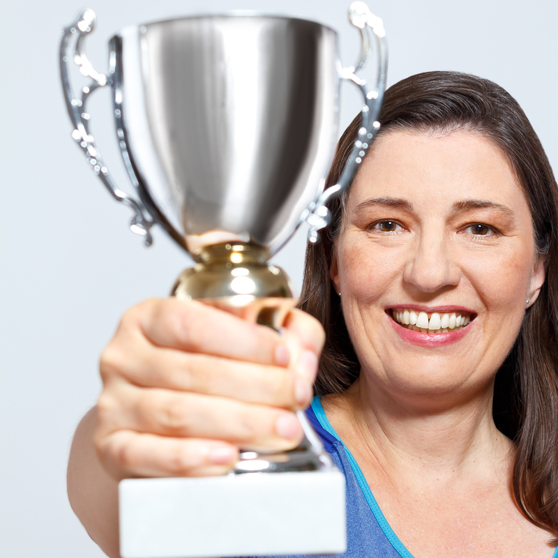 Image of woman holding up a trophy