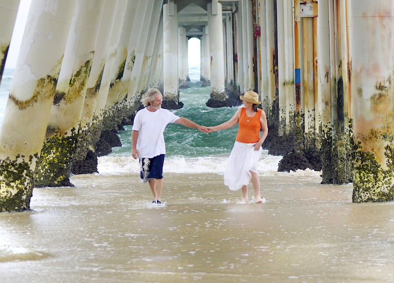 Couple holding hands and walking on a beach underneath a boardwalk