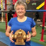 Barb holds a weightlifting trophy