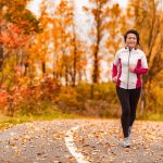 a woman in a track suit runs outdoors surrounded by fall foilage