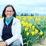Nurse Nicole Vienneau sits smiling in a field of daffodils