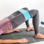 a woman wearing a resistance band demonstrates a glute bridge exercise on a mat