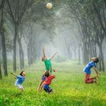 four children play with a ball outdoors, surrounded by trees