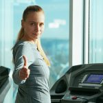 a blonde woman on a treadmill turns and gives a thumbs-up to the viewer