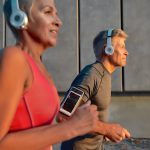 a middle-aged woman and middle-aged man running with headphones on