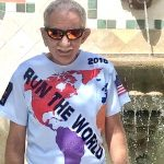 """an older man wearing sunglasses and a T-shirt with the words """"Run the World"""" printed on it"""